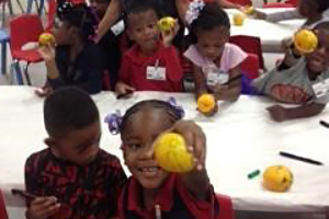 Program Dietitian Helen Woo and a Jutland Head Start Class Decorating Satsumas